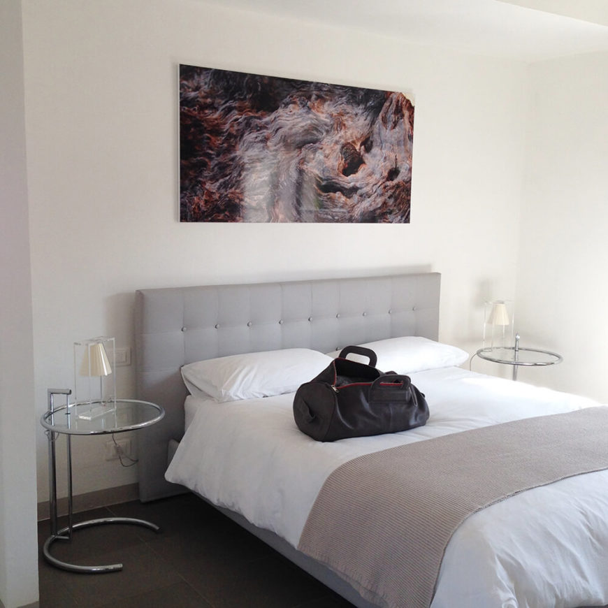 The bedside of the room. A tufted headboard softens the room and adds subtle color to the space. Again, vivid abstract wall art adds interest and color to the room.