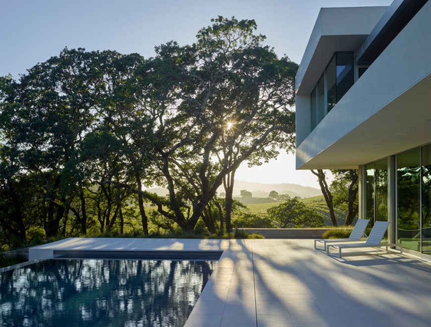 The poolside courtyard on this end of the home is an expansive, sleek area that complements the full height glazing well. With an infinity edge, the pool itself is a thoroughly modern piece of the design.