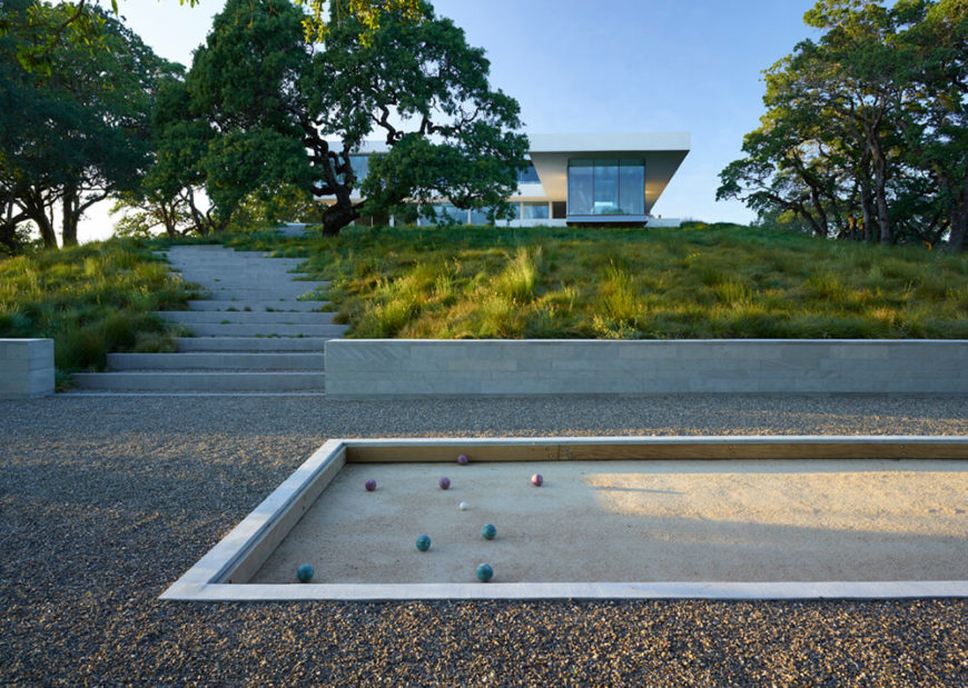 On the private side of the landscape, far from the hustle and bustle of the vineyard, we see a bespoke bocce ball court surrounded by a gravel courtyard. The home sits atop a hill, with the grassy landscape and large concrete stairs spilling down the slope.