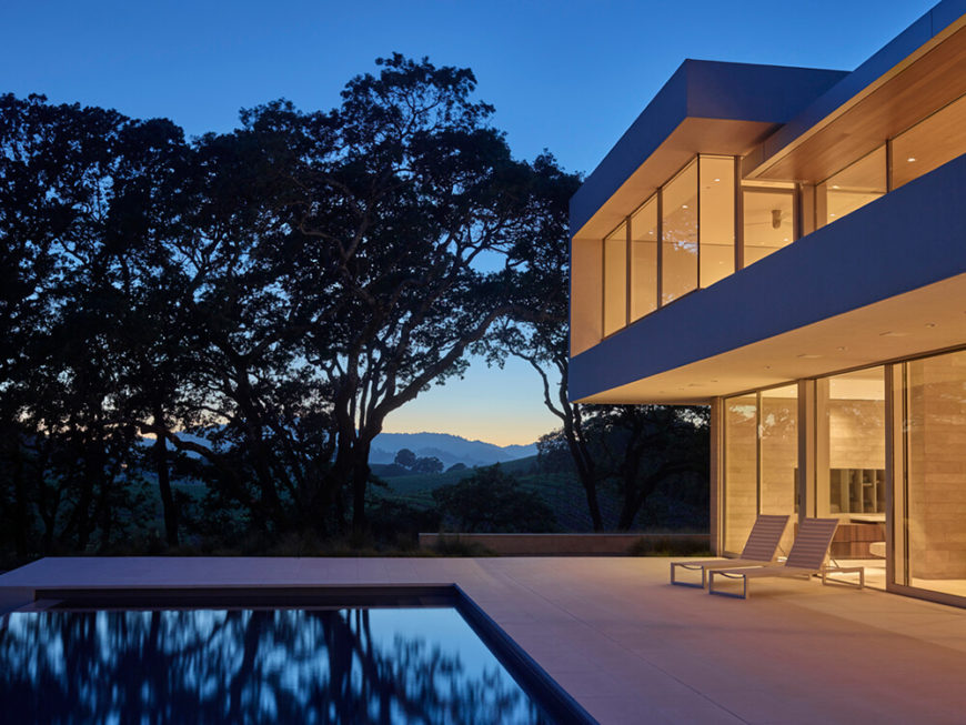 At dusk, a warm yellow glow from inside spills across the courtyard, throwing the nearby tree silhouettes into sharp relief. The great room and upper bedroom areas all feature direct views of the stunning landscape.