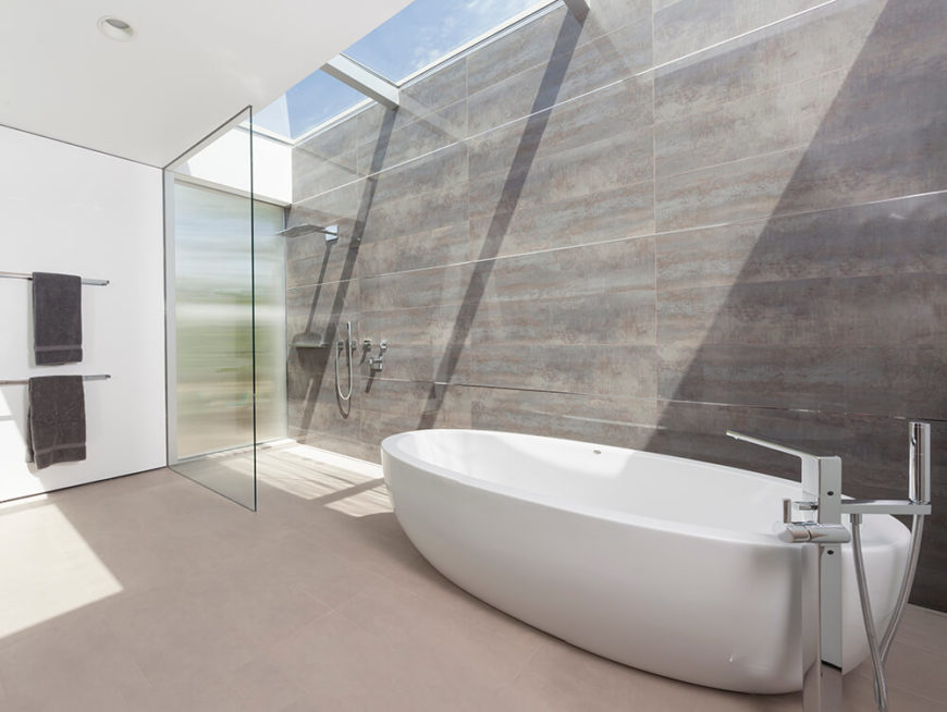 The master bath is an immense minimalist space, filled with concrete, glass, and white walls. A room-length set of skylights ensures natural light in daytime, glowing over the walk-in shower and large white pedestal tub.