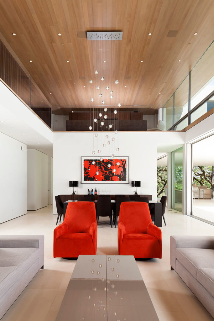 With ultra-light hardwood flooring and rich natural wood ceiling panels, this modern white space is bracketed by the warmth of traditional materials. The subtle use of red, on the club chairs and painting in the background, acts as a hot counterpoint to the sleek minimalist style.