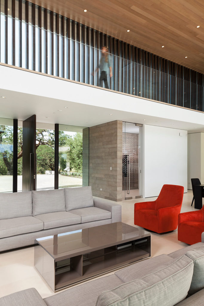 Across the set of contemporary furnishings, we can see the glass-wrapped front entry and a unique wine storage room to the right. Above, the second floor catwalk is partially sheltered by the wood panels dotting the exterior, offering shade and privacy.