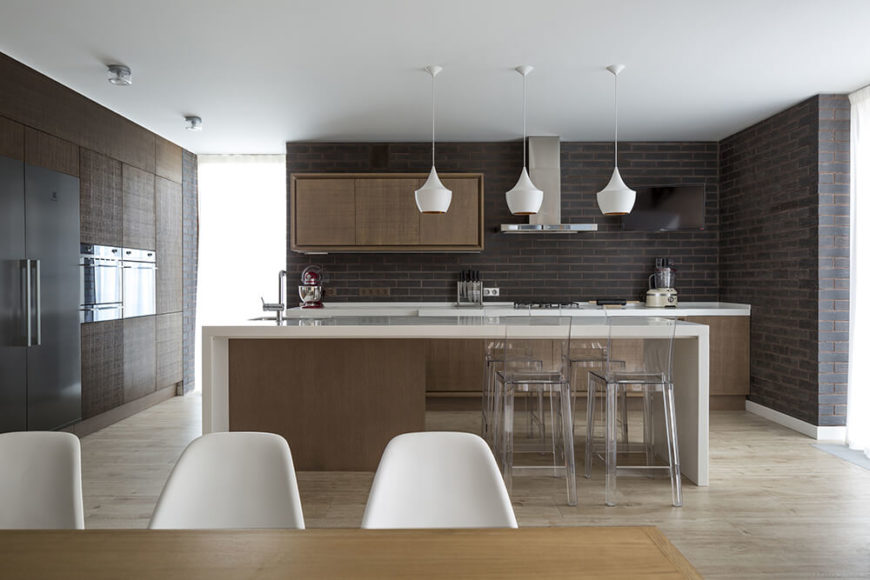 The brickwork continues into the kitchen and dining room, adding texture to the minimalist wooden cabinets. The preparation area is kept somewhat separate from the pantry. A spacious wood and white island has dining space for four, in addition to the more formal dining area adjacent.