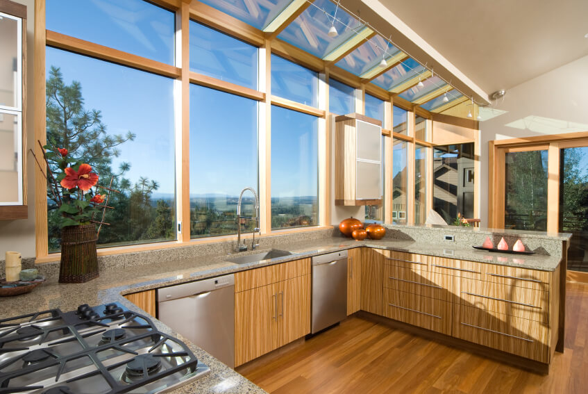 The vast array of large windows creeping up to the ceiling overhang illuminate this kitchen with ample sunlight. The granite countertops wrap over natural wood cabinetry, with rich hardwood flooring connecting the expanse. You'll notice that even the large windows and doors are framed in a light natural wood.