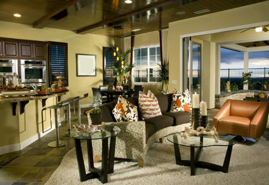 In an oddly shaped room, a diagonal kitchen island sits back to back with a curved contemporary sofa. The ceiling is polished, rich dark wood with several beams. To the right pocket doors lead out onto a spacious covered patio with a great view.