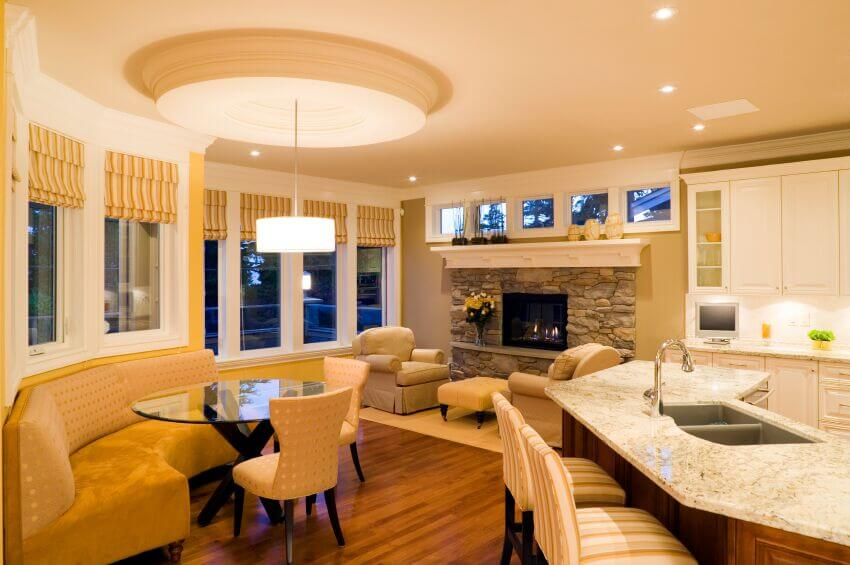 A small living room area is attached to a spacious white kitchen and is also open to a breakfast nook, which includes a circular glass-topped table and a spacious bench seat.
