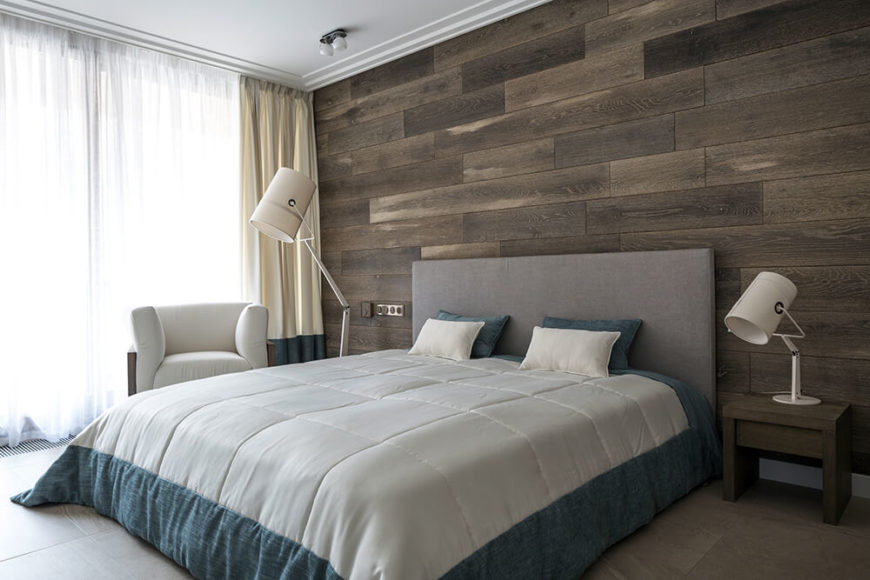 As we move into the master bathroom, we see another wooden plank accent wall, which contrasts with the gray fabric headboard. A matching floor lamp sits across the bed from the lamp on the nightstand.
