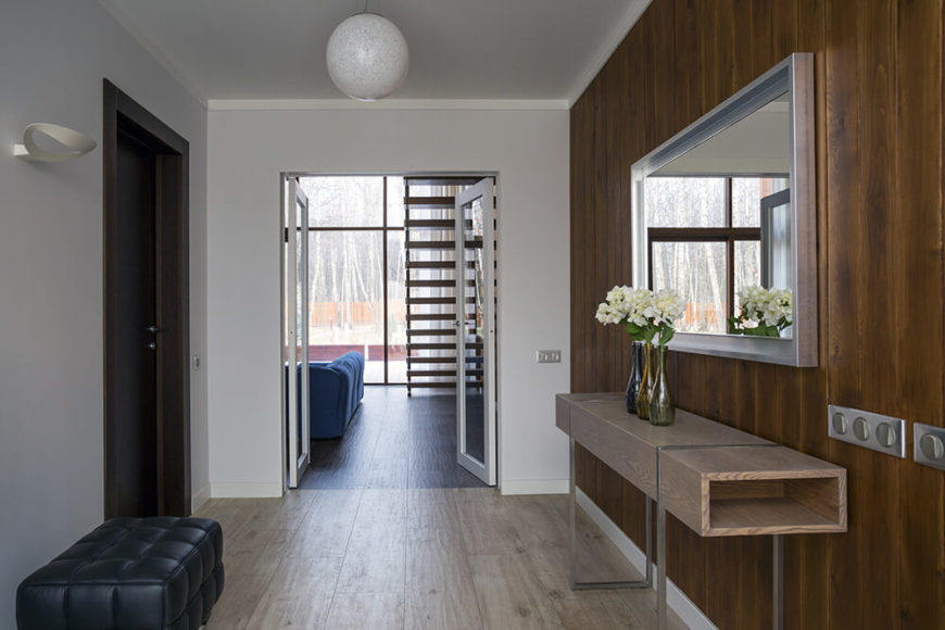 Entry to the home is provided through a wide hall, which features a larch plank accent wall with a minimalist table and a silver-framed mirror. The left wall is starkly minimalist in light gray. Glass double doors lead into the main floor living room.