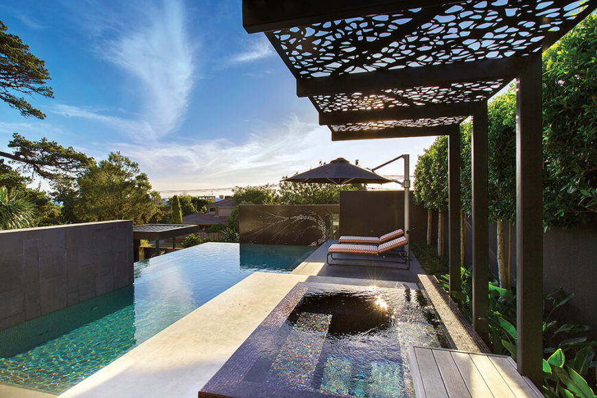 Along the side of the property, we see the privacy fence obscured by a row of trees and this free standing sun shade, cut with organic shapes. The jacuzzi mirrors the infinity edge design of the main pool.