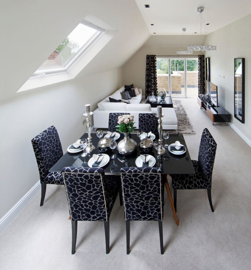 In a stark white room with a partially slanted ceiling, contrast is injected by way of a dark smoked glass dining table and deep blue giraffe-print upholstered chairs.