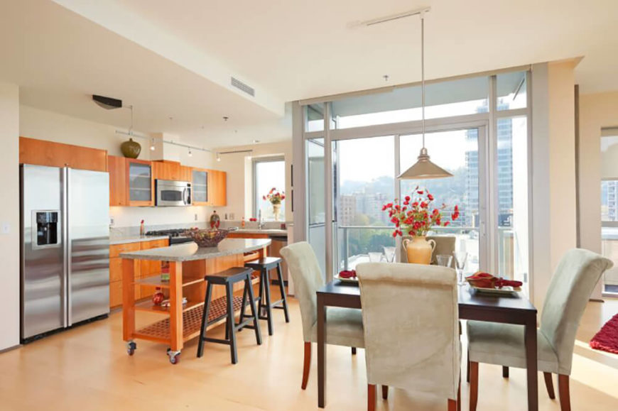 In a modern high rise home, the open plan design incorporates a kitchen, living room, and dining area at center. The dining table features dark wood, contrasting with the light shade of the kitchen, and is wrapped in grey fabric upholstered chairs.