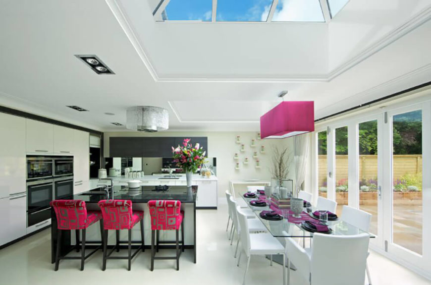 The sleek black and white contrast of this open plan dining room and kitchen is shot through with a splash of bright color, courtesy of the pink overhead lighting, table settings, and brightly patterned upholstery of the bar stools at left.