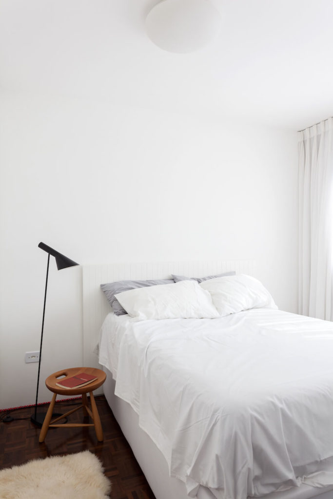 The minimalistic bedroom is laced in cloud-white colors. The parquet dark hardwood flooring contrasts well with the white linens and walls.