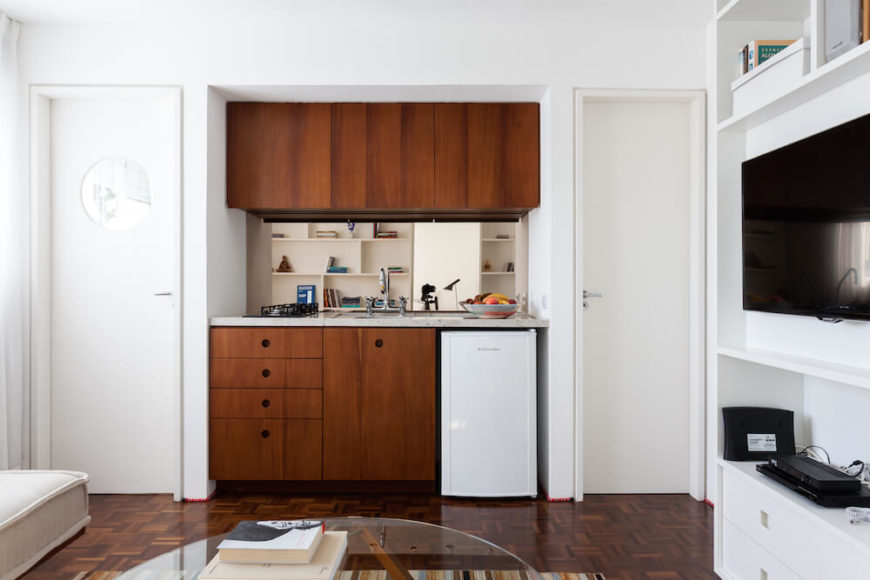 We can see the other side of the communal area, where the kitchen sits. Natural wooden cabinets and drawers create seamless storage above and below the counter space. The area is centralized and symmetrical with the rest of the home.