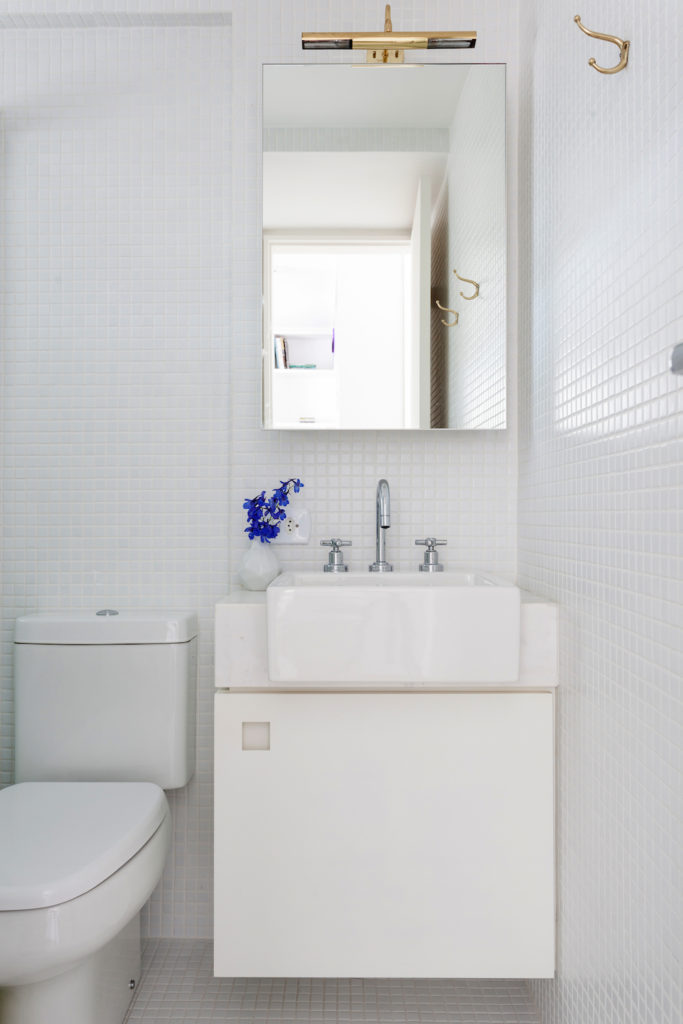 The bathroom is absolutely elegant. Dressed in all white tiles that move from the floor and all the way up to the ceiling, this space is flawless. The addition of a wild flower creates that classic bright addition of color to a white room.