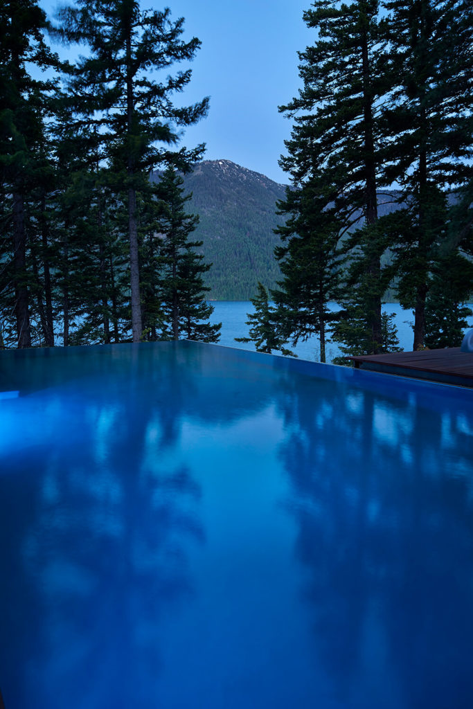 The edge of the shaded infinity pool looks out over the lake and lines up with one of the surrounding peaks.