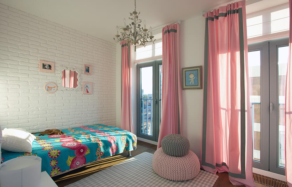 Charming master bedroom with a blue bed placed on the white brick walls. It includes two woven bean bags and floor to ceiling gray paneled windows covered with pink curtains.