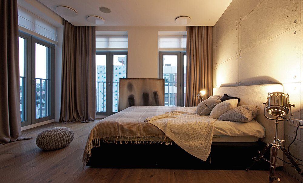 Sophisticated master bedroom with industrial touches from the accent wall and steel tripod floor lamps. It has a canvas art piece that lays on the wall which adds personality to the room.