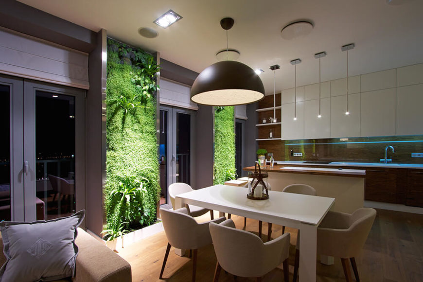 If we move around the table to the left, we can see the way each vertical garden is lit, making them incredibly vibrant, especially in the evening. We can also see the enormous light above the dining table, which contrasts with the much more minimal lights above the kitchen's island.