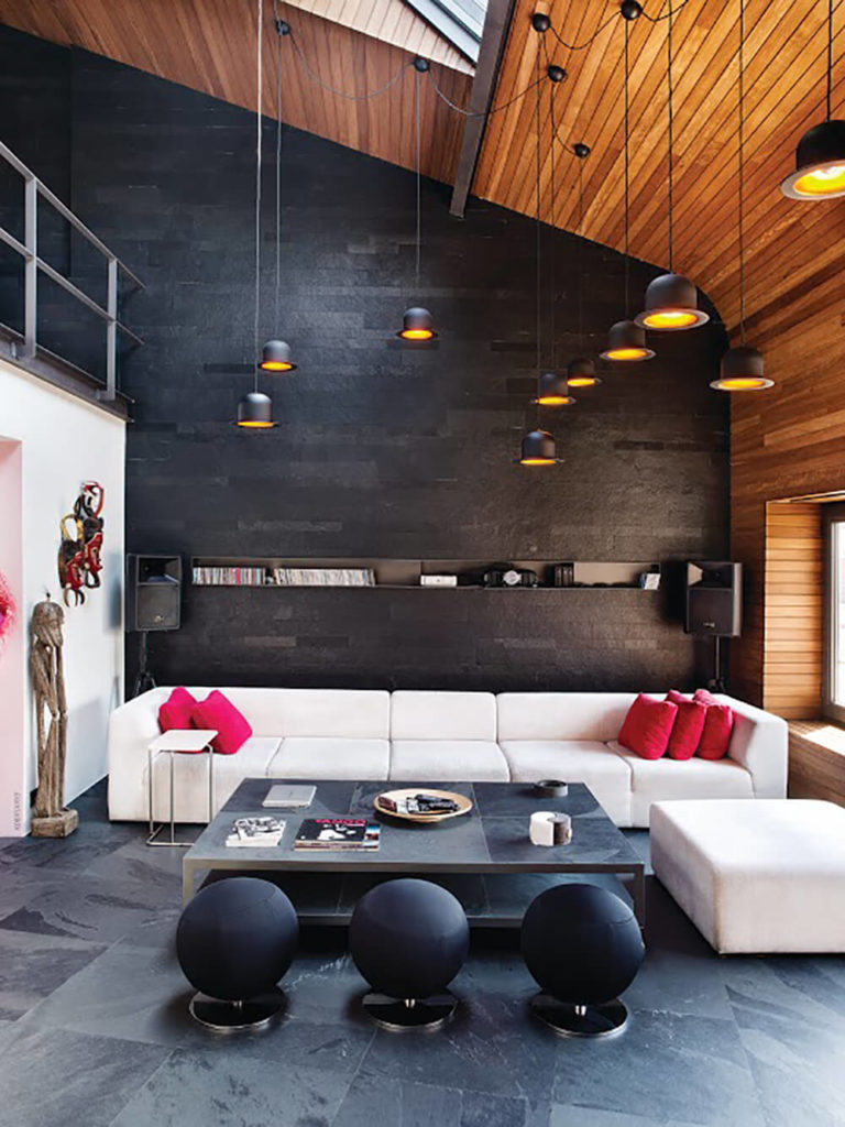 Turning the opposite direction in the mezzanine area, we see a white contemporary sectional wrapping a stone surface coffee table with a trio of spherical ottomans. The black wall at this end is nearly uniformly plain, in contrast with the storage all at the opposite end of the home.