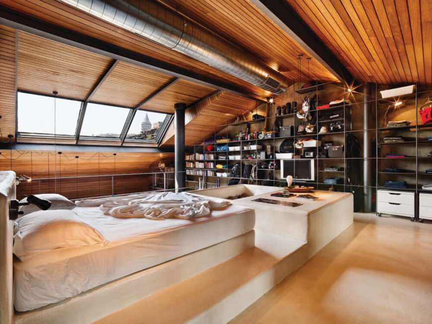 The master bedroom sees the bed mounted on a concrete bock platform, commanding the center of the space. The rich wood panels of the exterior walls reach all the way to the peak above this room.