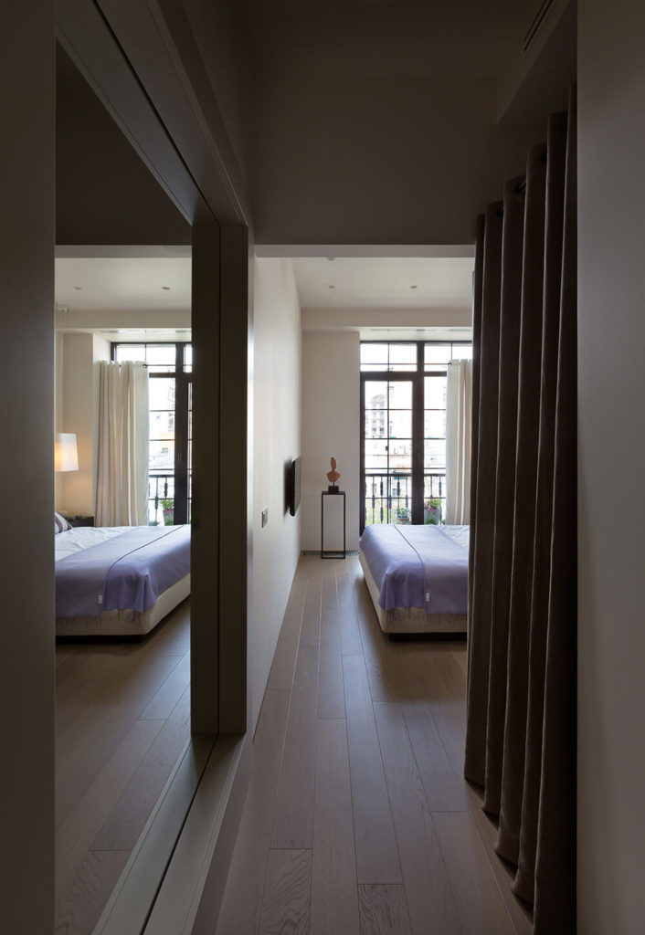 Moving down the hall to the private half of the home, we come to the master bedroom. This large space is illuminated with sunlight through the glass French balcony doors. The light hardwood flooring from the living room continues uninterrupted here.