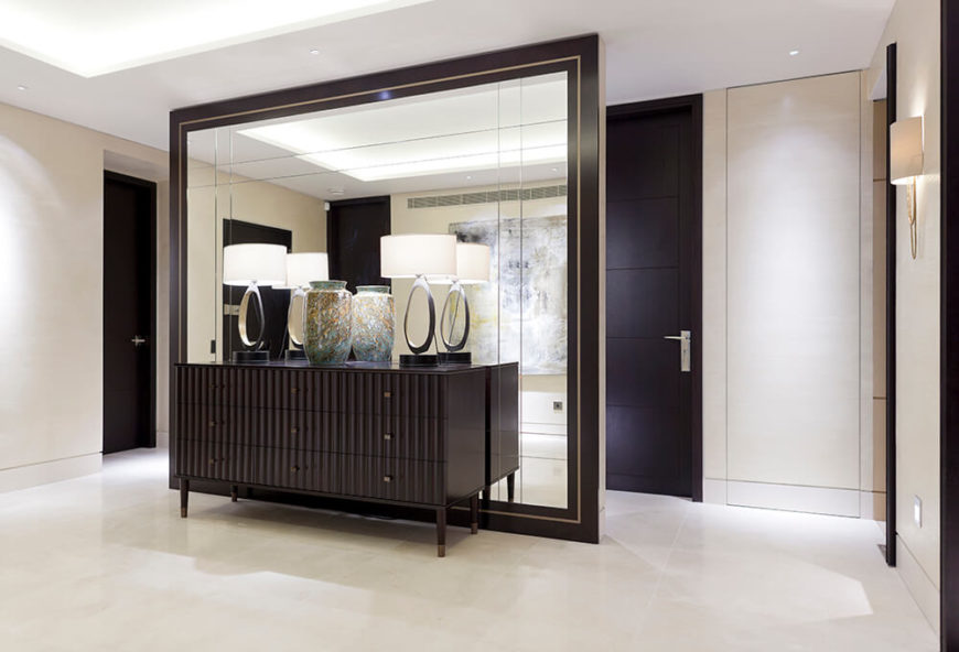 This free standing mirror wall both obscures and expands the visual space in the social area of the home. Framed in a deep black, with decorative elements on a dark dresser in front, it's an essential component of the design.