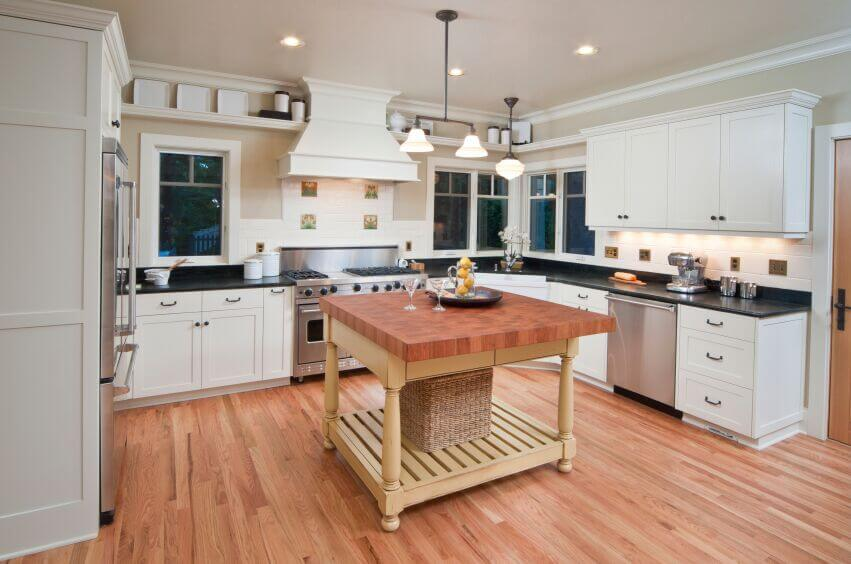 The dark counters in this kitchen break up the white of the cabinets and keep it from being overpowering. The wood of the floor and the island countertop warm up the room while the butter-yellow of the island's base adds a touch of color.
