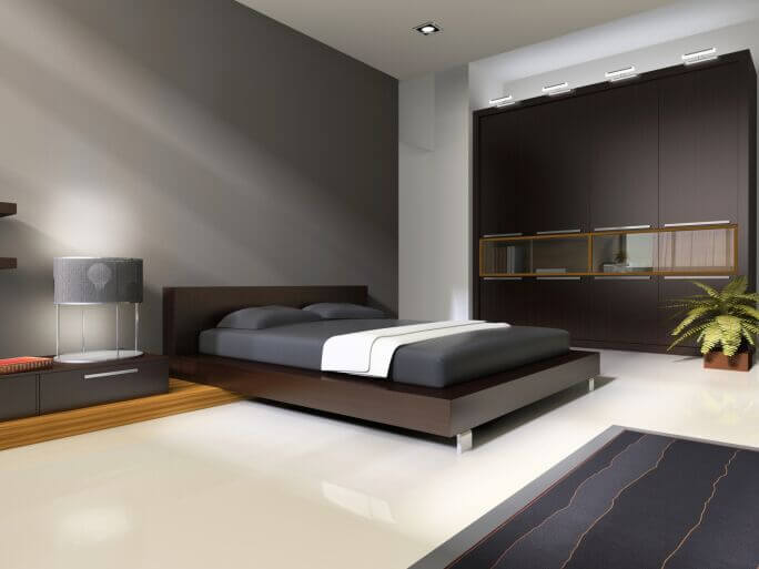 Sleek and minimalist, this modern bedroom features sparse but sharply defined appointments across its expansive white flooring. A massive bookshelf wall features windowed compartments sandwiched between closed door cabinetry.