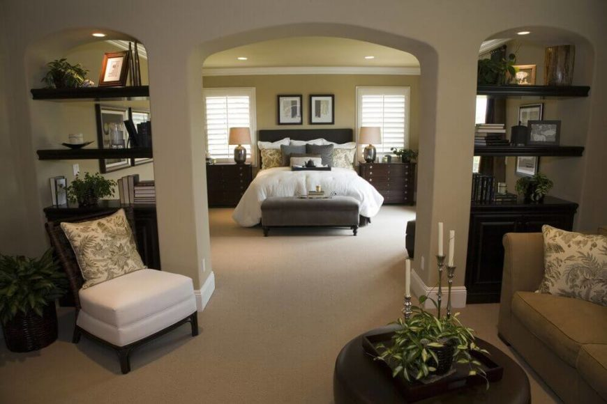 Seen through an exquisite archway dividing the broad space, this bedroom features a pair of gorgeous dark wood built-in bookshelves flanking the archway. The shelving and cabinetry match the elegant tone of the bedside dressers and large circular ottoman.