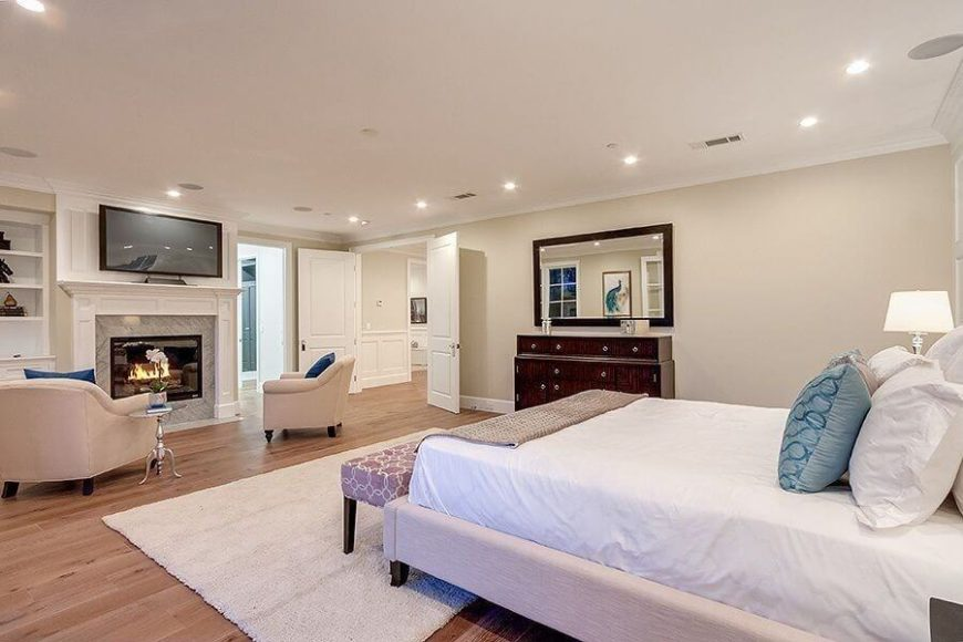 This expansive bedroom en suite features light natural hardwood flooring and soft eggshell walls, with a marble wrapped fireplace at center. Next to that is a set of built-in bookshelves in white, matching the doors and framing seen throughout.