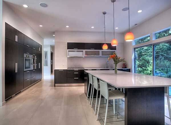 This brightly modern minimalist kitchen features dark wood cabinetry against white walls and flooring for ultimate contrast. The island extends into a massive dining table with white surface, below a set of pendant lights.