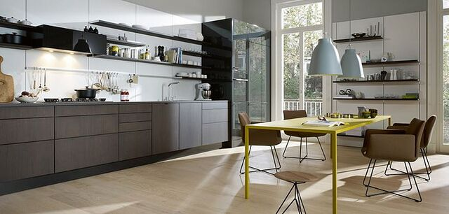 Here's a sleekly modern kitchen with hardware-free cabinetry and a minimalist shelving system, mounted directly to the walls. A bright yellow dining table offers a splash of color and contrast.