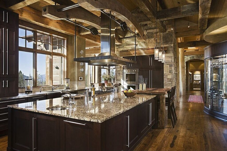 Here's a truly grand and luxurious kitchen, filled with rustic and modern elements. Hardwood flooring, dark wood cabinetry, and granite countertops inform the textures, while a rustic wood dining table stands next to the massive island.