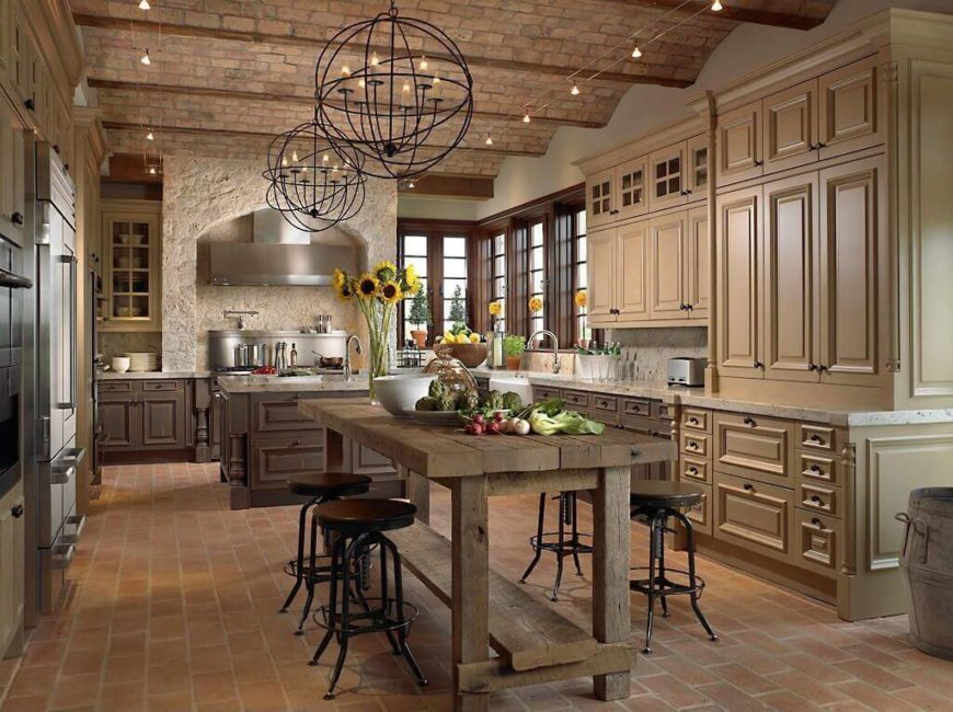 Deep luxury and rustic style meet in this vast kitchen, where beige and dark natural wood cabinetry meet over a red brick floor. Both a marble topped island and rustic wood dining table fill the floor space.