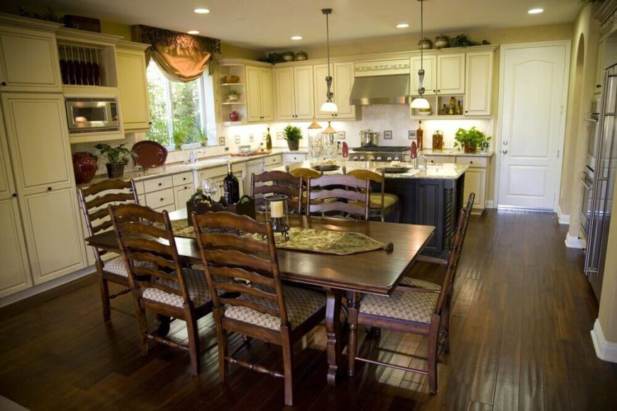In a wide, traditionally styled kitchen, there's plenty of floor space for the large dark stained wood dining table, wrapped with ornate carved chairs. Along with the hardwood flooring, this adds dark contrast to the light cabinetry seen throughout.