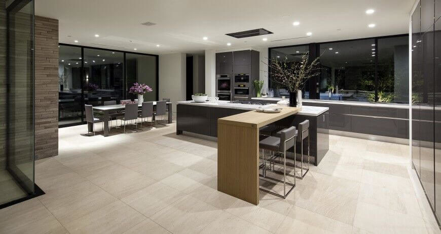 Large format beige tile flooring underpines an expansive kitchen design, features a large island with raised natural wood extension at center. A full size dining table adds additional function to the massive kitchen.