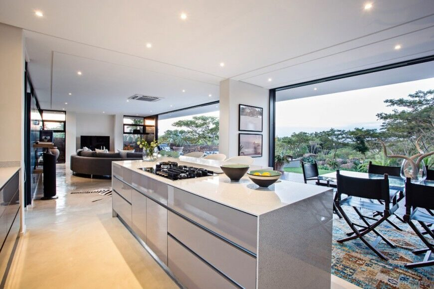In a massive open-plan space that's opened to the elements via large sliding glass panels, the kitchen is defined by its large white-countertop island with built-in range. The dining table sits to the right in all glass, with canvas seat chairs surrounding.