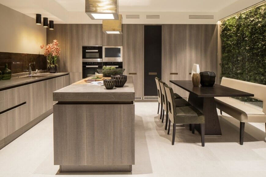 This ultra-modern kitchen uses light grey natural wood on all cabinetry and the island, over a white tile floor, offering an elegant and neutral look. The dark wood dining table is seated with a bench on one side, beneath a massive full height window.