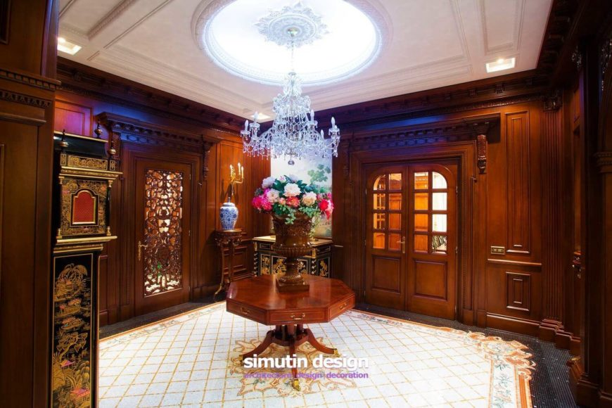 The gilded single door leads into the crossroads of the home. A crystal chandelier hangs above a beautiful wooden octagonal table in the center of an ornate mosaic tile floor. Doors lead into other rooms on the home's main floor.