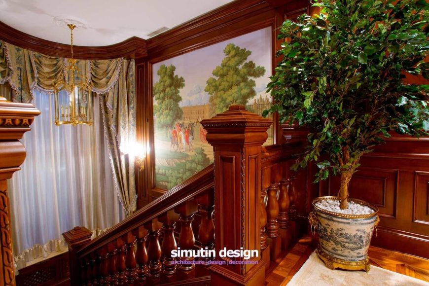 At the top of the staircase, the mosaic tile of the previous floor transitions into a rich parquet floor covered by a luxurious rug. An ornamental potted tree rests in the corner, complementing the large trees in the mural beyond.