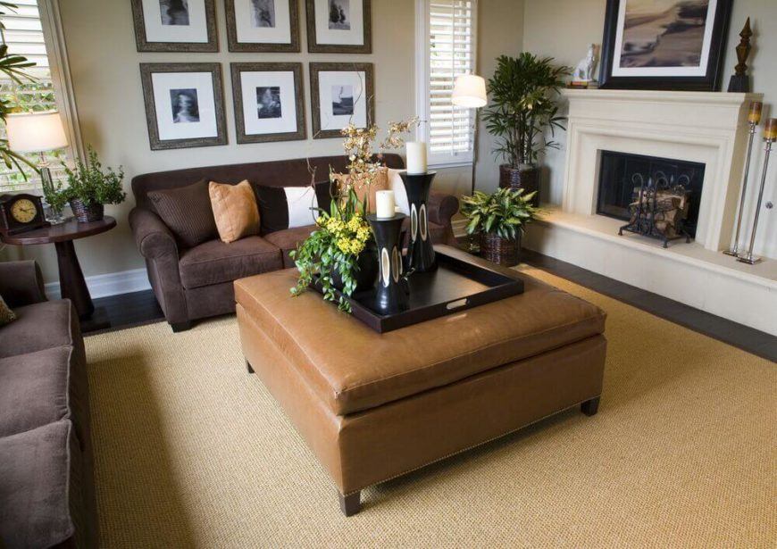 A much lighter brown ottoman doubles as a coffee table between two chocolate-brown velour sofas. To the right is an elevated wood-burning fireplace. A lighter brown ottoman allows for accent pillows in a matching shade to pull color to the darker sofas.