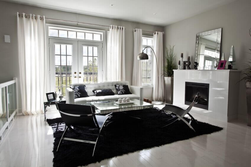 An Incredibly Stark White Living Room With French Doors Leading To A  Terrace. Paired With