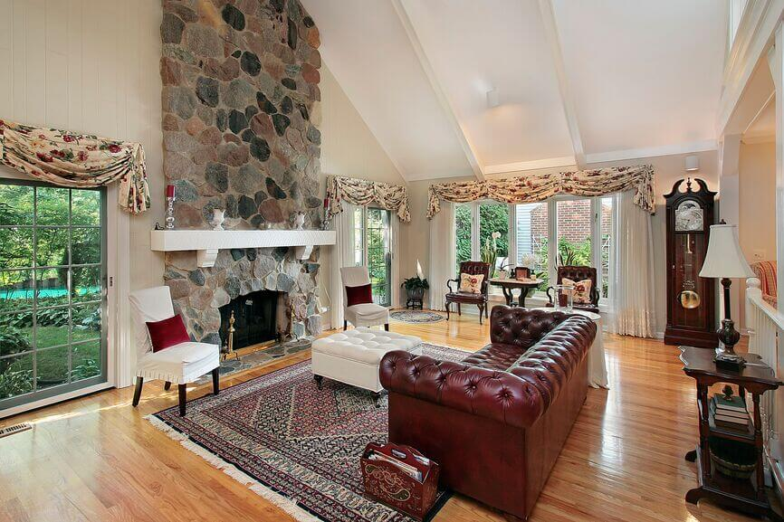 Leather Sofa In A Spacious Traditional Living Room With A Stone Fireplace.