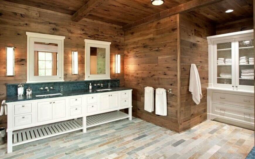 Contemporary multi-tonal tile floors are paired with rustic wooden walls. Country-style sinks and mirrored medicine cabinets create a fully functional and stylish master bathroom.
