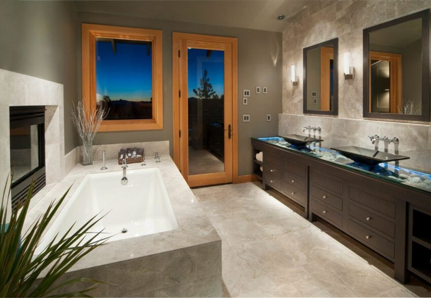 This beautiful tile and wood bathroom features an enclosed fireplace above the gorgeously deep soaking tub. The vessel sinks rest on a translucent glass counter. Beneath the glass are stones backlit by a bright blue light.