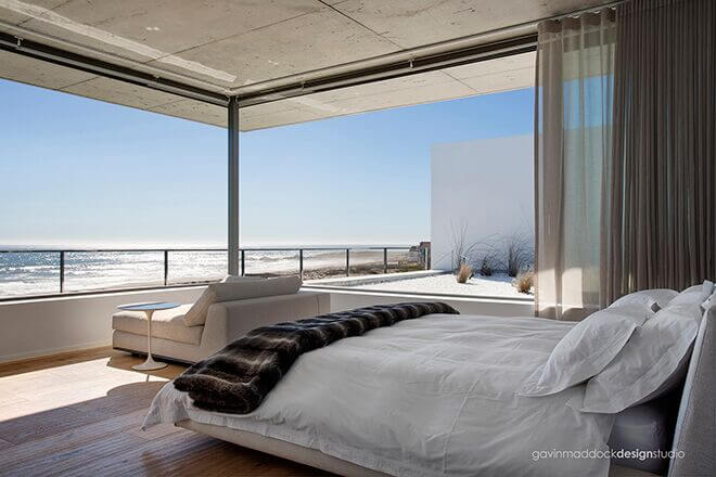 This simple room utilizes furniture with a low profile and light color to show off the stellar view of the beach and ocean.
