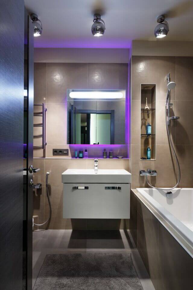 This narrow bathroom is made more interesting by the addition of a purple backlit vanity mirror to include a pop of color in the room. Sleek and modern, this bathroom utilizes a more minimalist design while still being able to include all the amenities that one comes to expect in a bathroom.