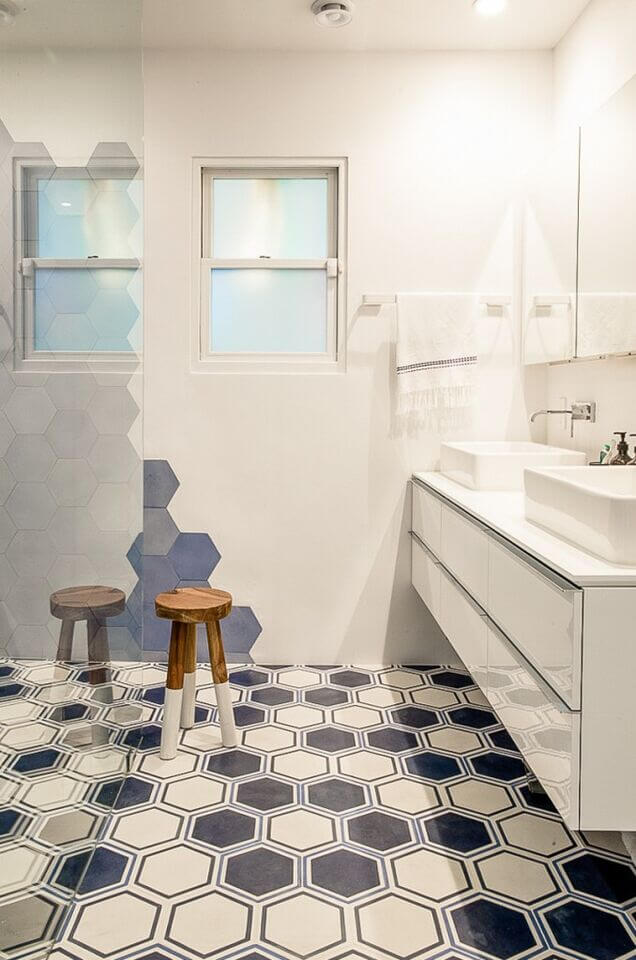 This minimal white bathroom utilizes a navy blue honeycomb pattern on the floor and tiled on the wall to create a contrasting design to the extensive use of white.